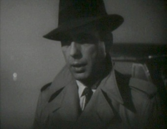Humphrey Bogart in the iconic fedora & trench coat, often worn by noir private eyes (image is in the public domain)