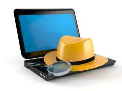 hat and magnifying glass on computer