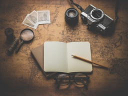Notebook, camera, magnifying glass on ancient map